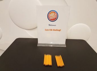 a sign on a brown table with 3 pencils infront.